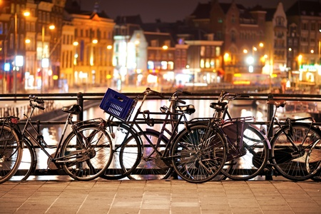 Bikes parked on a bridge at night in Amsterdam