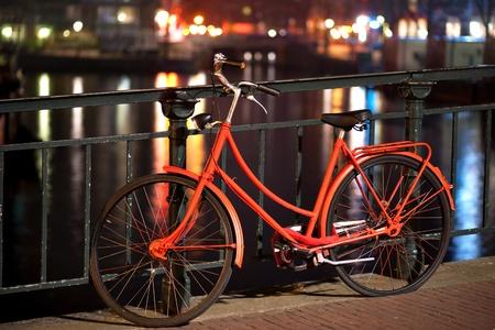 Pomarańczowy rower na most nad kanałem w Amsterdamie