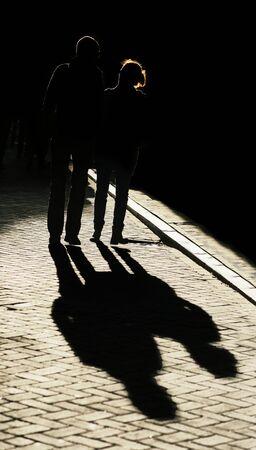 couple lit: Silueta de la joven pareja caminaba por una calle en la luz de la tarde