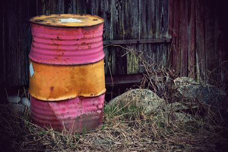 hazardous: colorful rusty metal barrel in front of wooden shed