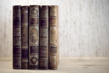 libros antiguos: Fila de libros antiguos en el estante de cuero