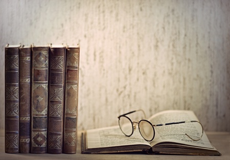 library old: Vintage books and glasses on desk Stock Photo