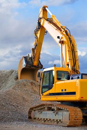 maquinaria pesada: Excavadora amarilla con gran montón de grava en el cielo azul