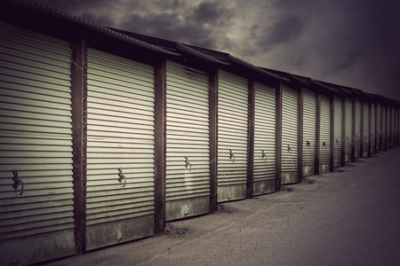 Row of metal garage doors in run down residential area