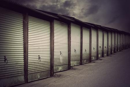 Row of metal garage doors in run down residential area