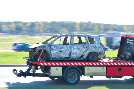 Wrecked and burnt car being transported by pick up truck Stock Photo - 13460573