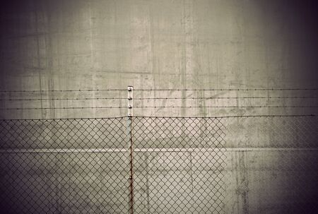 tatty: chain link fence and barbed wire on wintage background Stock Photo