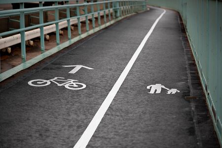 Painted signs on asphalt for pedestrian and bicycle lanes photo