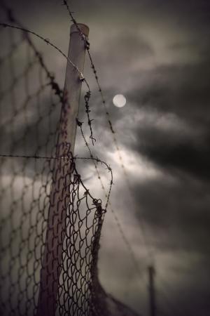錆びた有刺鉄線とチェーン リンク フェンスのヴィンテージと月で不機嫌そうな夜の空に見える 写真素材