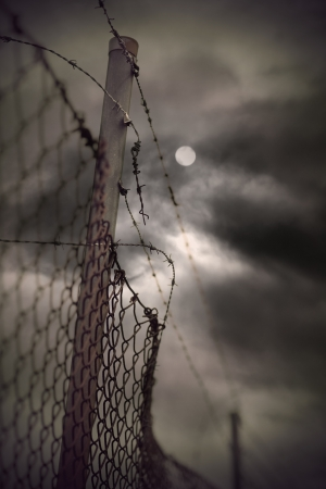 Rusty barbed wire and chain link fence with vintage look on moody evening sky with moon Standard-Bild