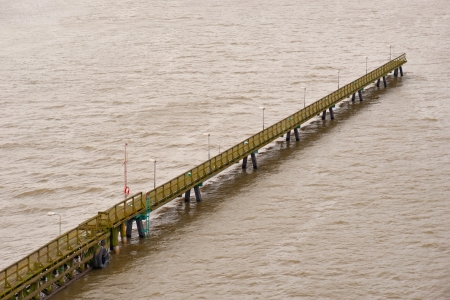 Long old wooden pier in troubled water photo