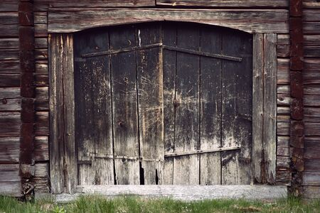 flaking: black ancient wooden grunge door on timbered wall