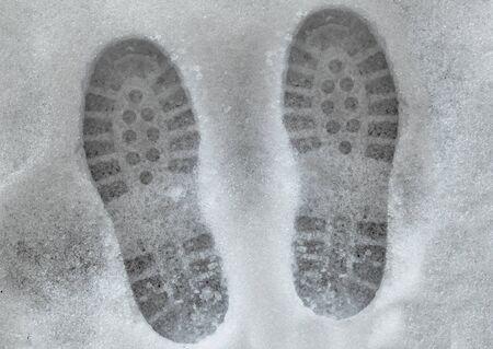 shoeprints in melting snow on asphalt photo