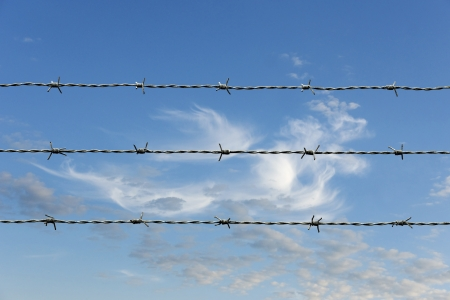 barbed wireon blue sky with fluffy clouds photo