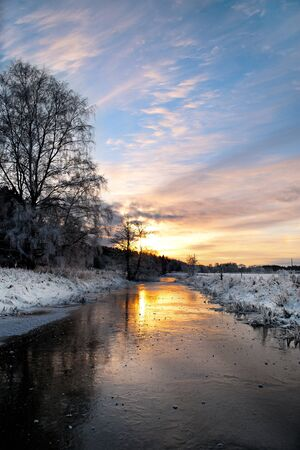 rime frost: sunset at small rural river with trees with rime frost Stock Photo