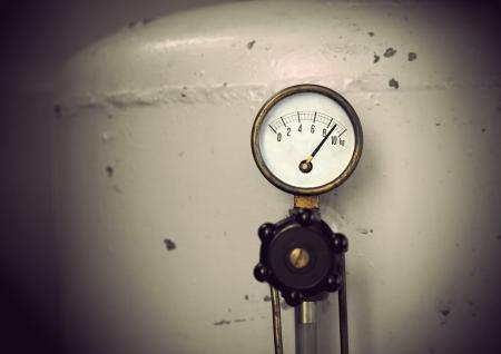 preassure: Vintage pressure meter on metal water tank Stock Photo