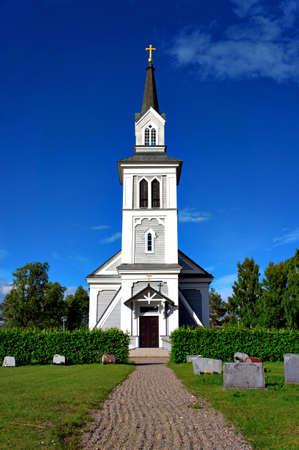 Beautiful wooden country church with cemetary photo