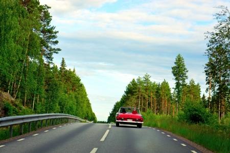 Red vintage cab sports car on rural asphalt road