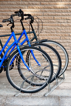 parked bicycles: Front wheels of three bicycles in bicycle stand  Focus on middle bike  Stock Photo