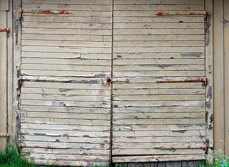 Garage door with peeling yellow paint and rusty metal details photo
