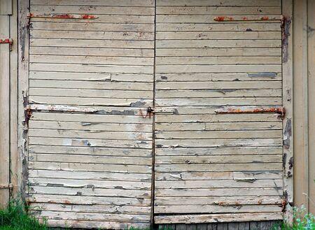 Garage door with peeling yellow paint and rusty metal details photo
