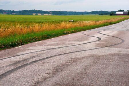 Tire prints on asphalt road in rural landscape  Focus on prints  photo