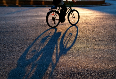 Shadow of cyclist on city street in evening light  Focus on shadow Фото со стока