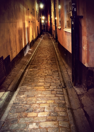 Narrow street with cobblestones in old town of stockholm at night photo