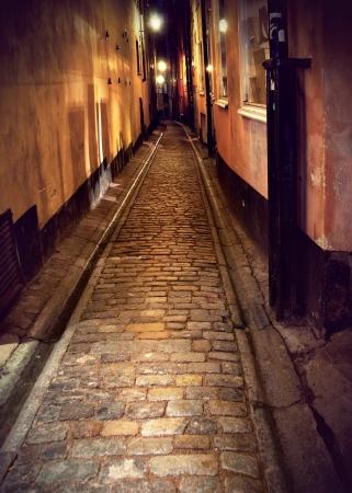 Schmale Straße mit Kopfsteinpflaster in der Altstadt von Stockholm in der Nacht