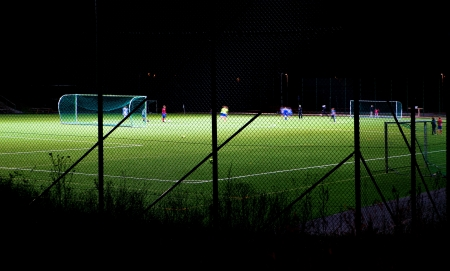 junior soccer: A team of young players practicing soccer at night