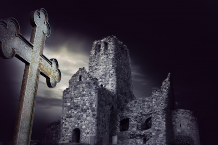 Spooky ruin with metal cross in foreground photo