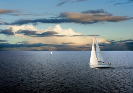 bateau: Des voiliers voguent sur la mer avec le ciel nuageux Banque d'images