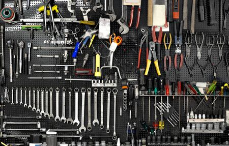 neat: Black wall with many tools in workshop Stock Photo