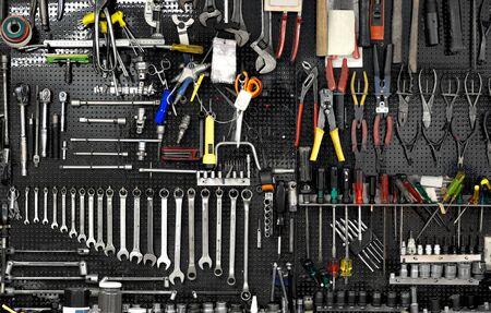 Zwarte muur met vele hulpmiddelen in de werkplaats Stockfoto