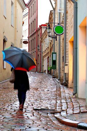 cobblestone street: Woman with umbrella on narrow street with wet cobblestones in Tallinn, Estonia