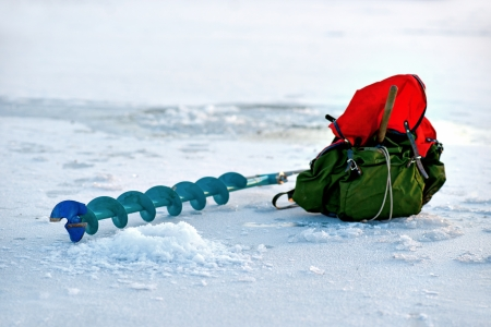 ruck sack: Auger and backback near a newly drilled hole in ice. Focus on hole and top of auger Stock Photo