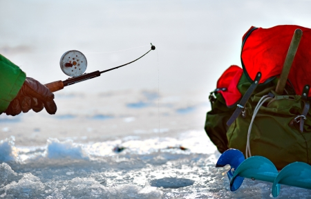 ice fishing: Hand of person fishing in a hole in ice Stock Photo