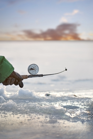 ice fishing: Hand of person fishing through a hole in ice Stock Photo
