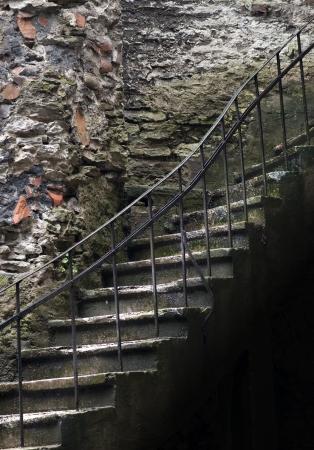 Alte Treppe mit Metall-Handlauf in spooky Kellern