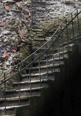 basement: Ancient staircase with metal hand rail in spooky cellars Stock Photo