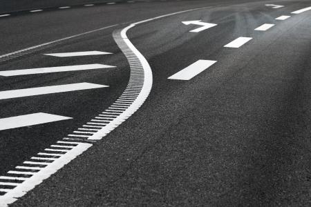 dividing: Close up of dividing line and arrow sign on asphalt road