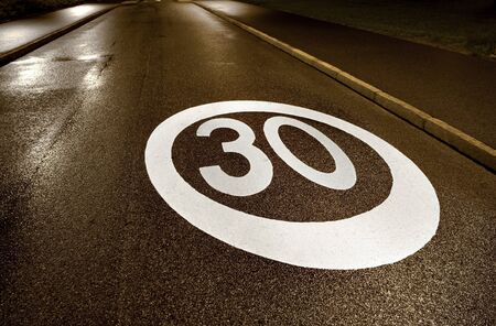 Speed limit painted on wet asphalt at night photo