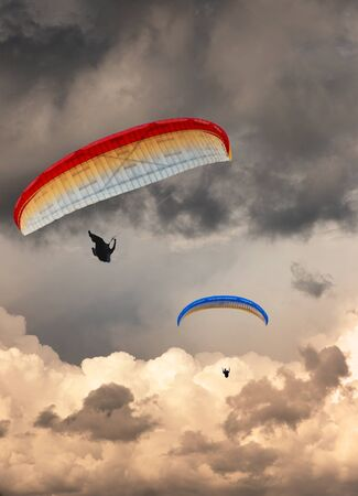 Two hang gliders at sunset with moody sky photo