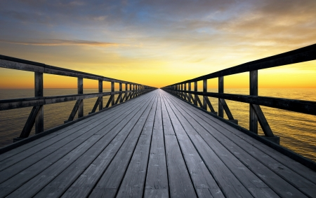 long lake: Long pier disappearing into orange sunset Stock Photo