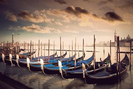 gondolas in a row in in sepia in Venice, Italy photo