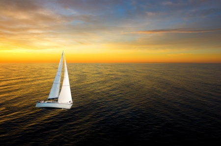 White yacht at golden sunset with wide horizon photo