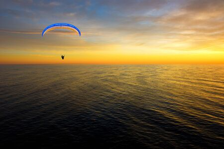 gliding: Hang gliding man over sea at sunset