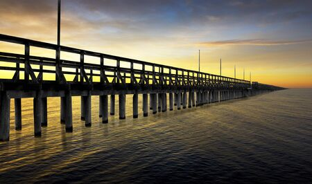 the long lake: Silhouette of very long pier in orange sunset Stock Photo