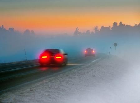 Achterlichten van auto op de weg in een donkere mistige winteravond Stockfoto