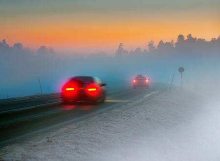 winter road: Rear lights of car on road in dark foggy winter evening